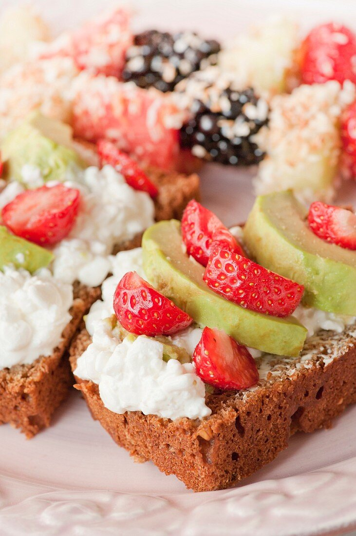 Rye bread with cottage cheese, strawberries and avocado; fruit and coconut skewers in the background