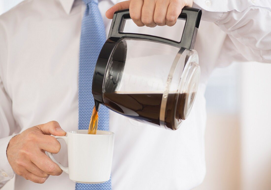 A man pouring coffee from a jug into a mug