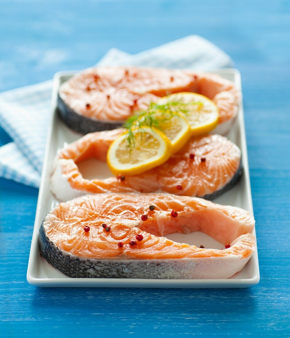 Three red salmon steaks on a porcelain train on a blue surface, with a napkin