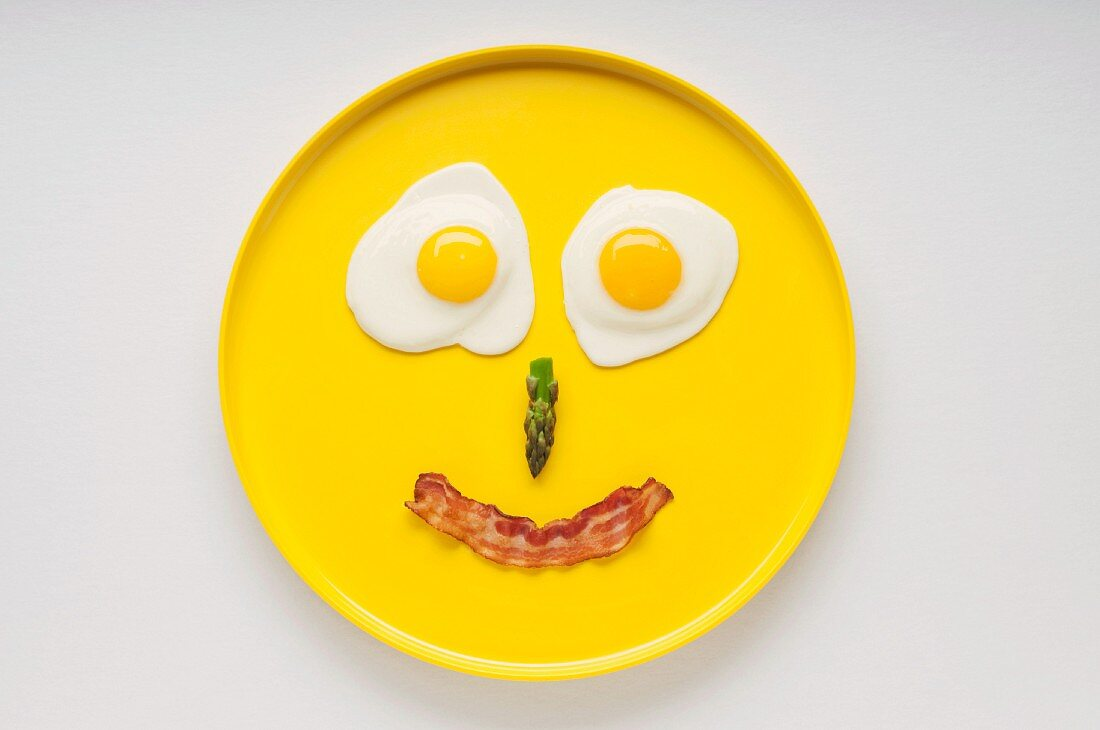 Smiley Face on a Yellow Plate Made from Two Fried Eggs, Asparagus and a Strip of Bacon