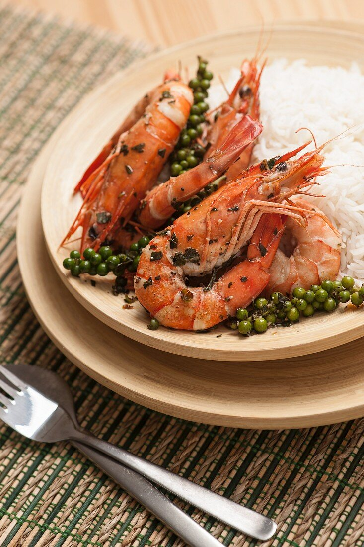Stir-fry king prawns with garlic, fresh green peppers and basil, served with jasmin rice on a bamboo plate. This Kampot green pepper prawns is a Cambodian traditional dish.
