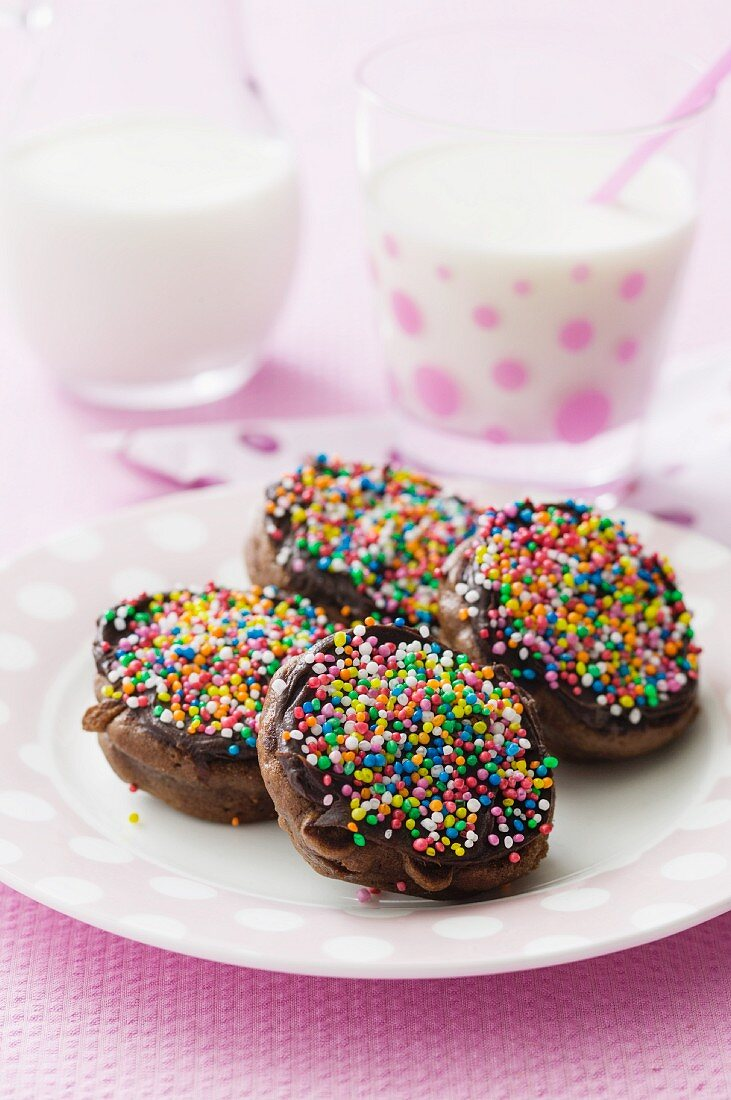 Chocolate pikelets with colourful sugar sprinkles, with glasses of milk in the background
