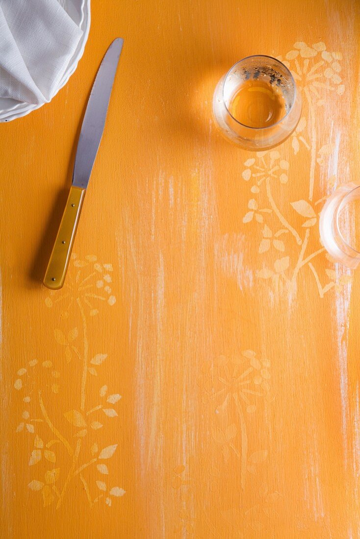 An orange surface with a flower pattern, a knife, stacked plates and a glass
