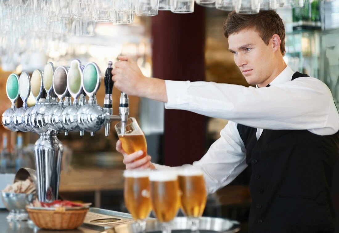 A waiter pouring draught beer in a pub