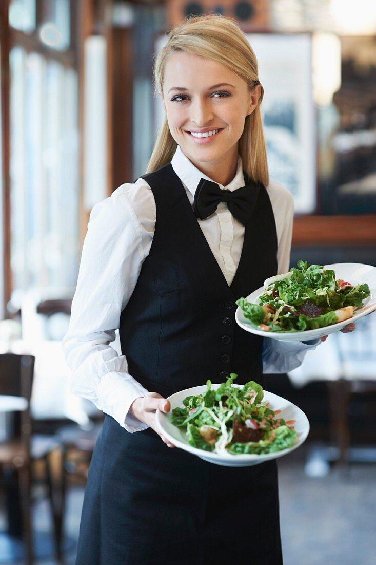 A waitress serving plates of salad in a pub