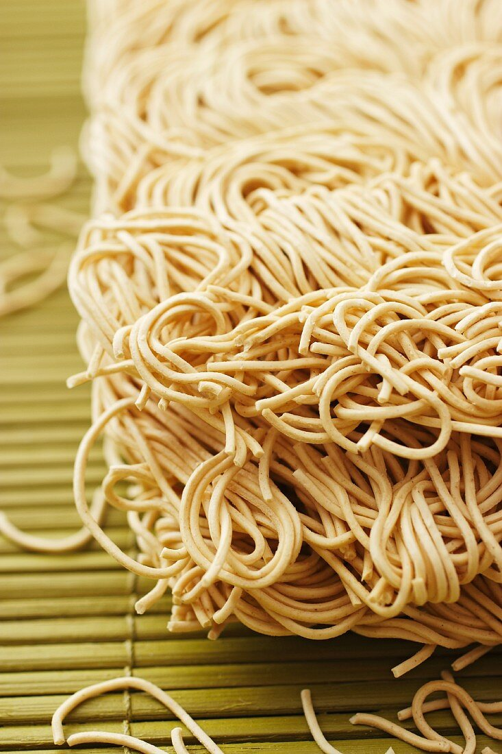 Chinese egg noodles on a bamboo mat (close-up)