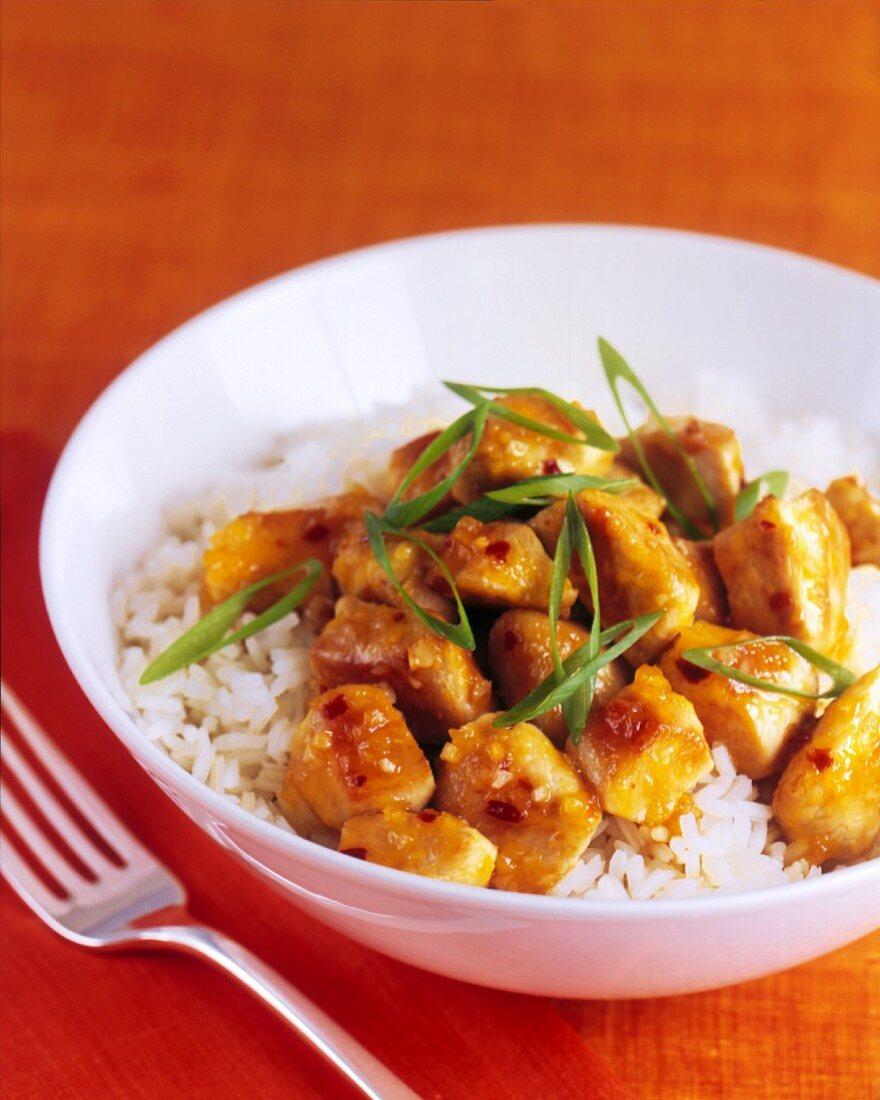Orange Glazed Chicken with Scallions Over Jasmine Rice; In a White Bowl