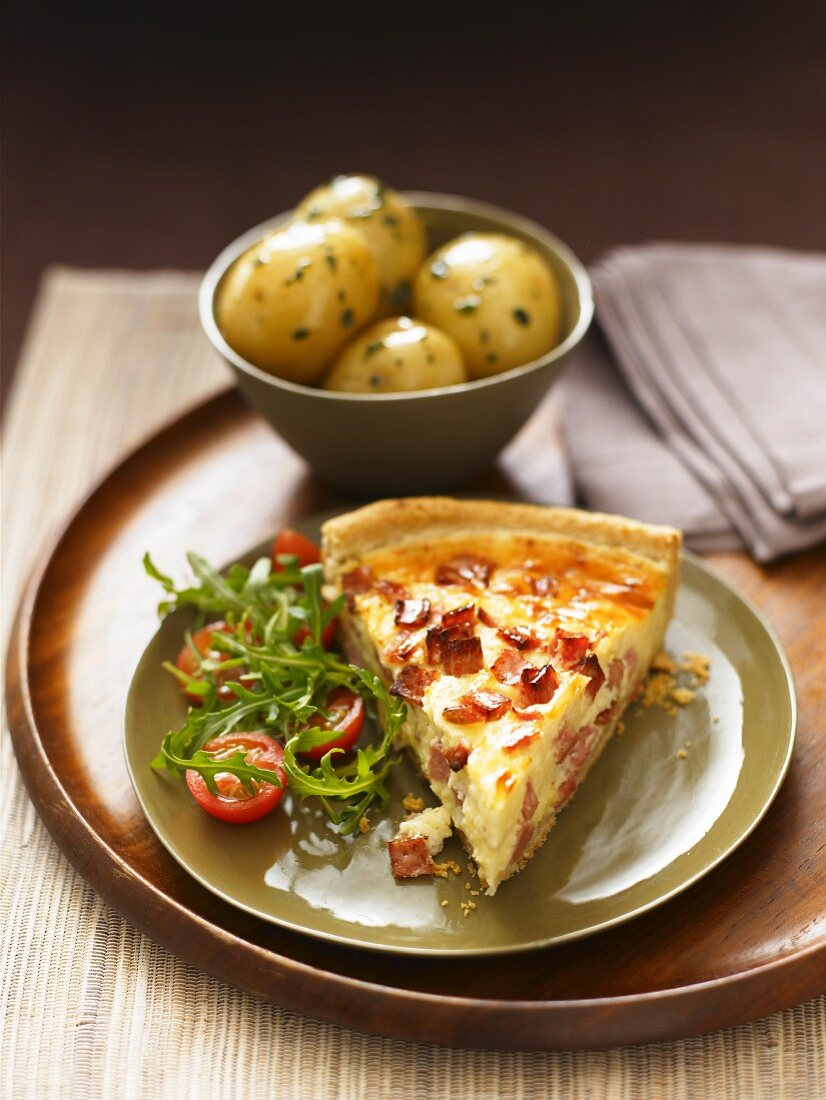 A slice of quiche lorraine with rocket salad and a side dish of potatoes