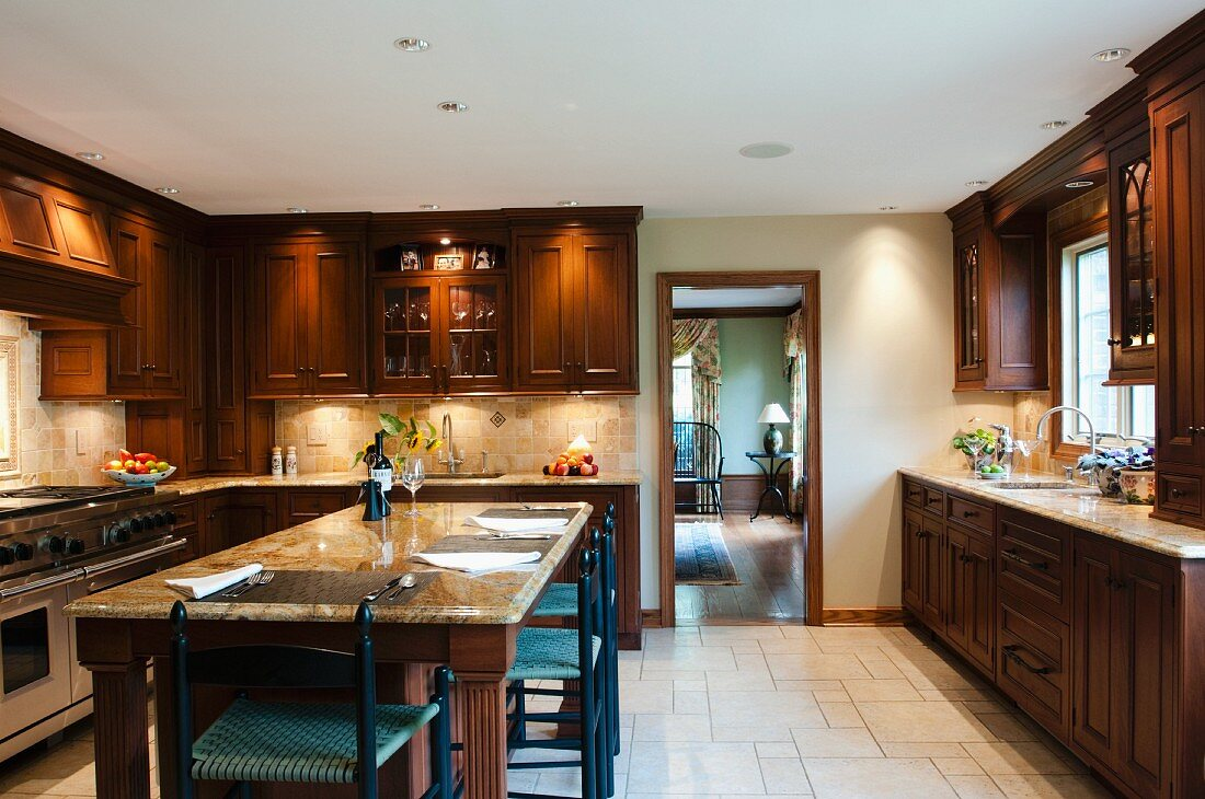 Country-house kitchen with dark brown, solid wood cupboard doors and marble-topped dining table
