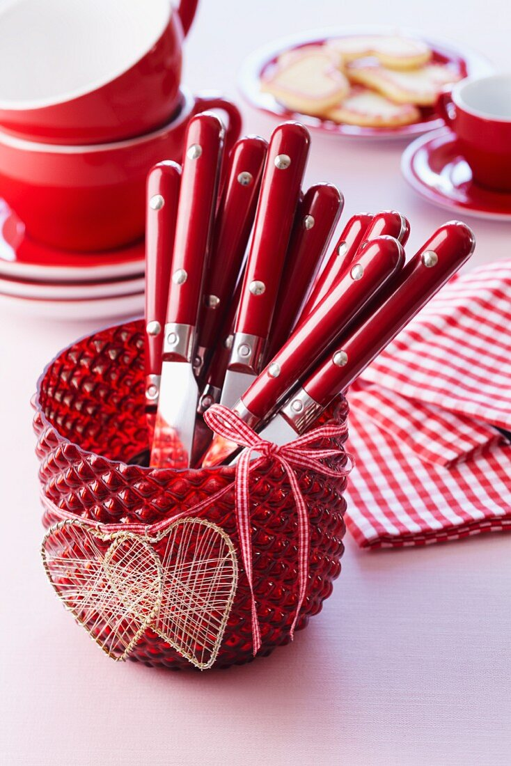 Red candle lantern with heart-shaped decorations used as cutlery holder