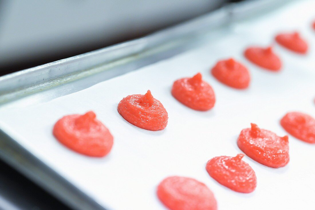 Blobs of batter on grease-proof paper for pink macaroons
