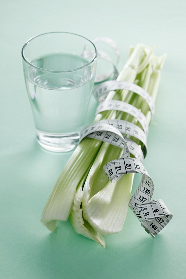 Celery with a measuring tape and a glass of water