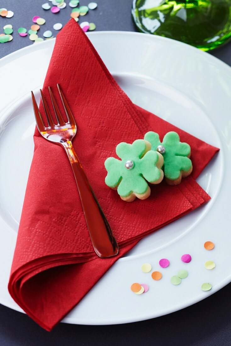 Clover leaf-shaped biscuits and confetti decorating a plate