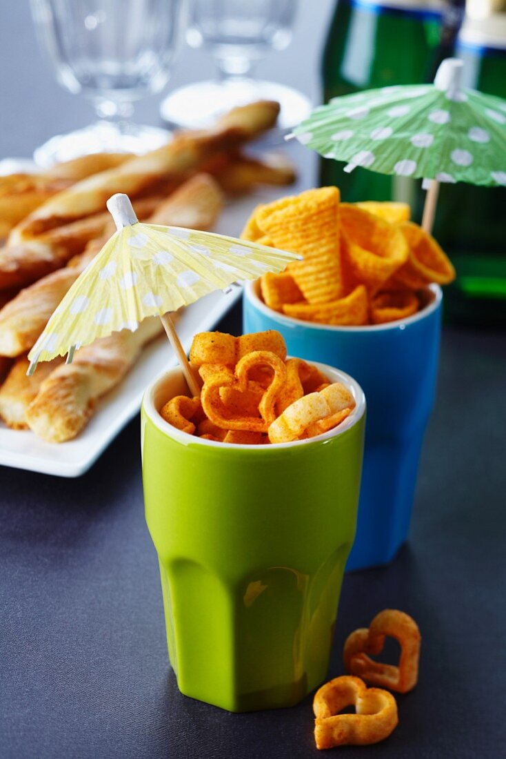 Snacks in cups decorated with cocktail umbrellas