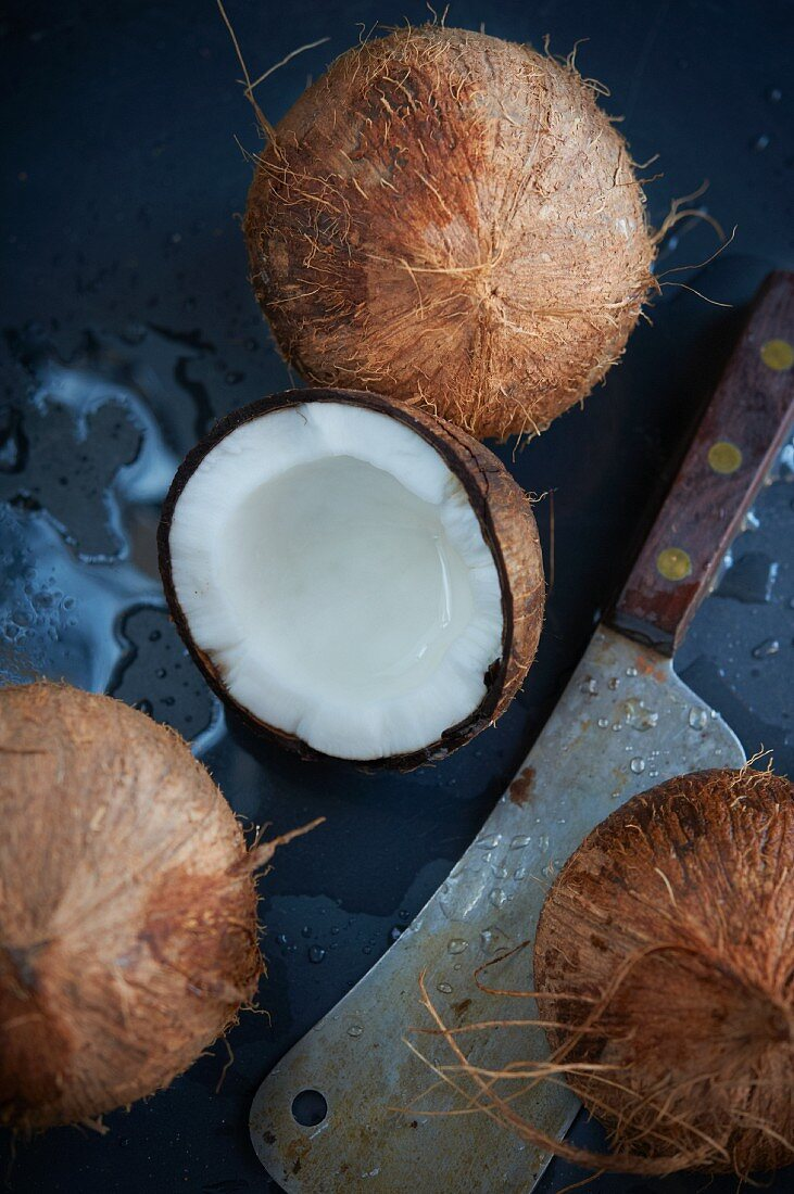 Fresh Coconuts with a Large Knife; One Cracked Open with Spilled Coconut Milk