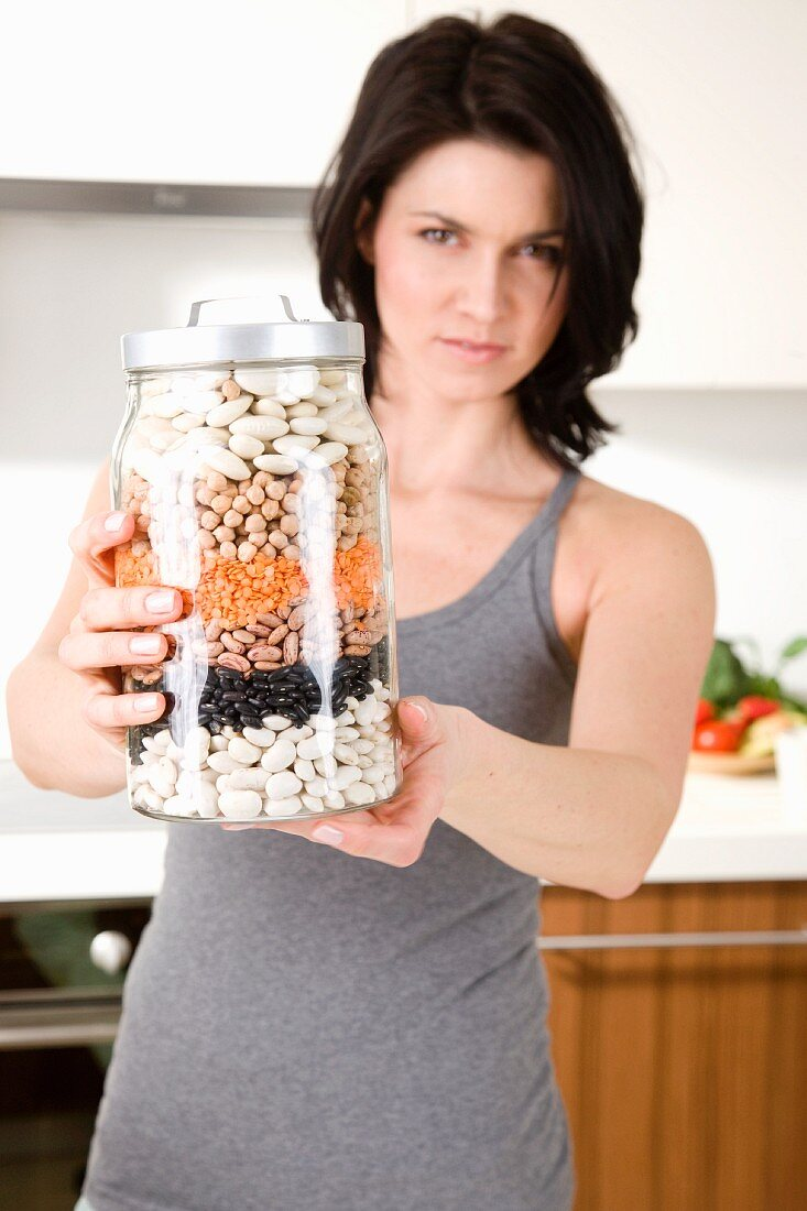 A woman holding a storage jar full of pulses