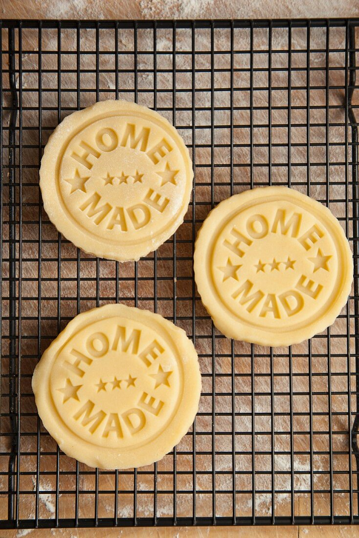 Biscuits stamped with 'home made', on a cooling rack