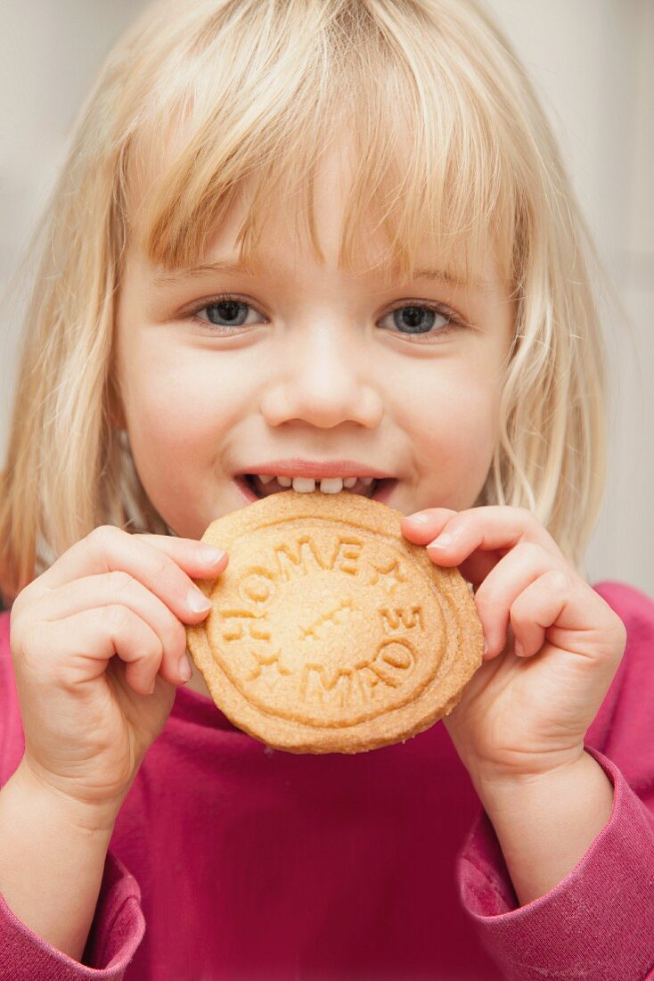 A young girl eating a home-made biscuits