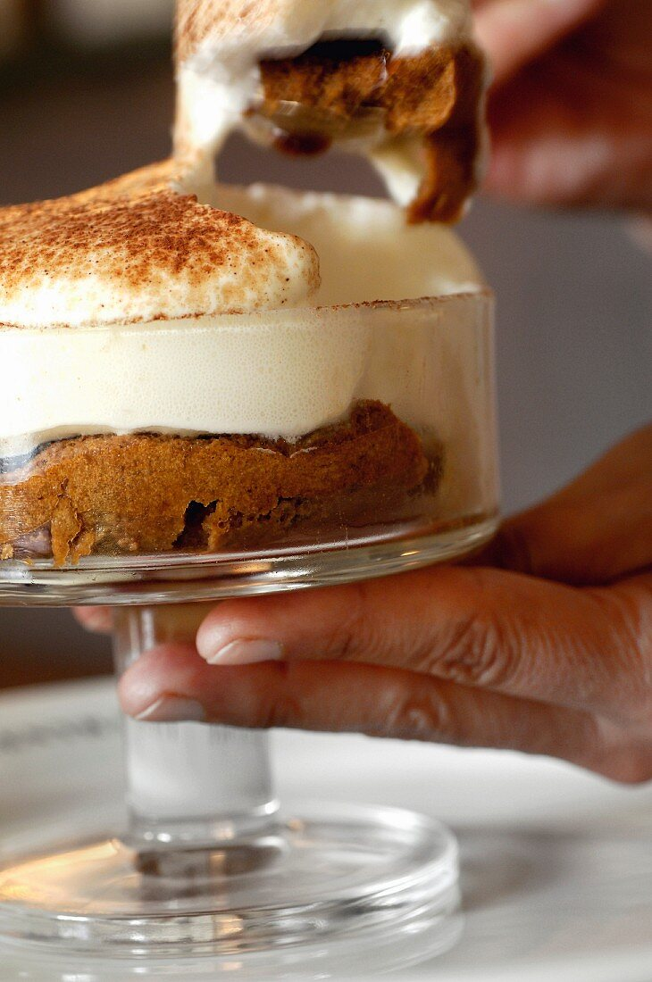 A spoonful of tiramisu being taken from a dish