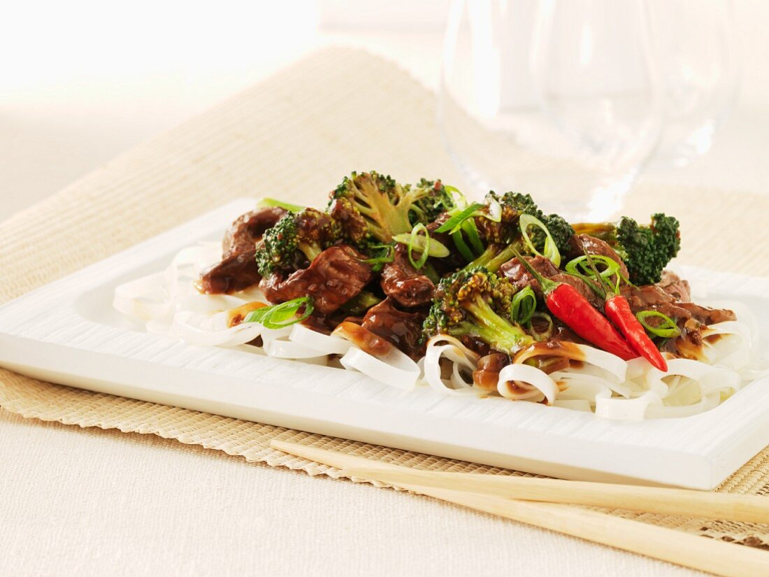Beef and broccoli stir-fry with chillies on a bed of rice noodles