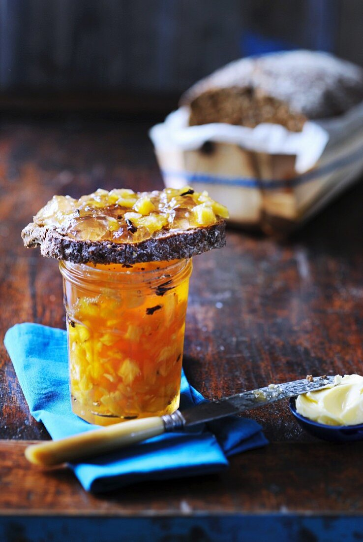 Pineapple jam with cloves in a jar and on bread