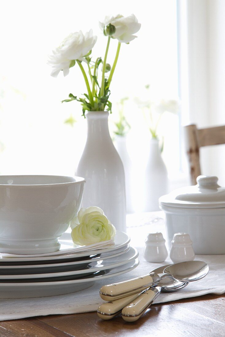 Stacked crockery and cutlery on a table with a vase of white ranunculus
