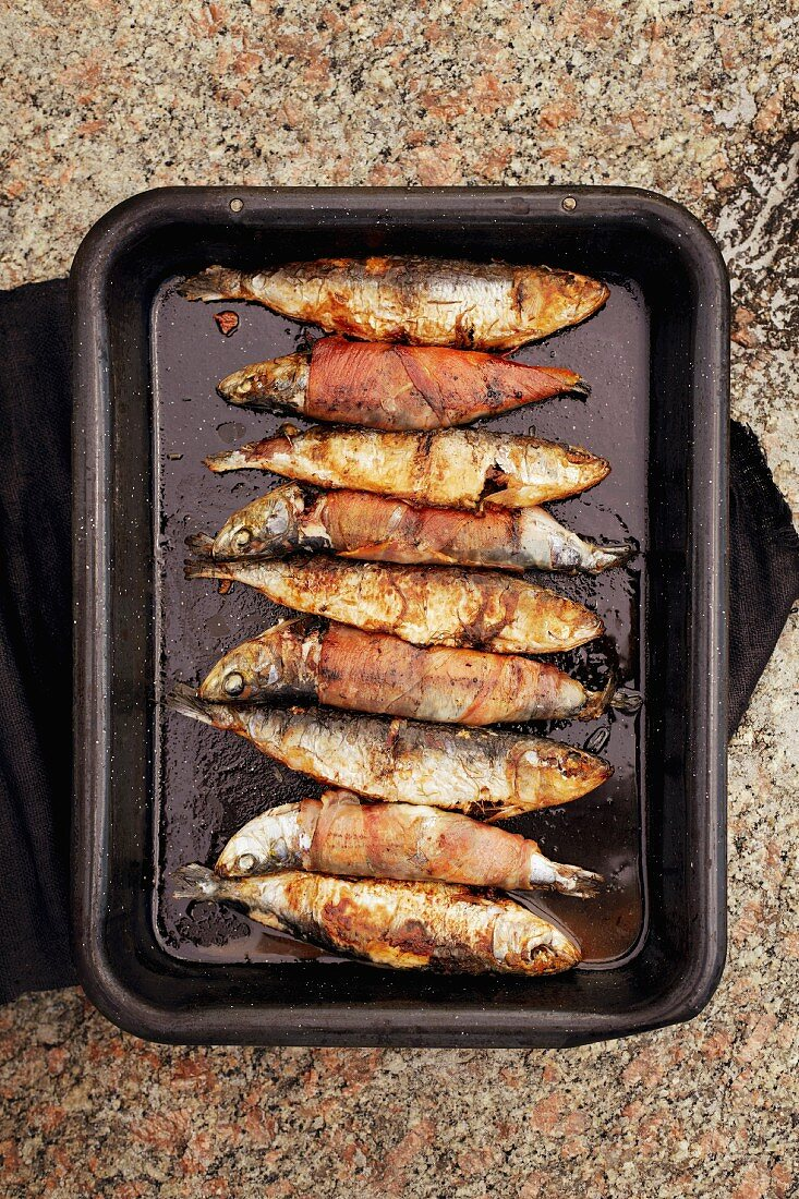 Barbecued fish wrapped in bacon