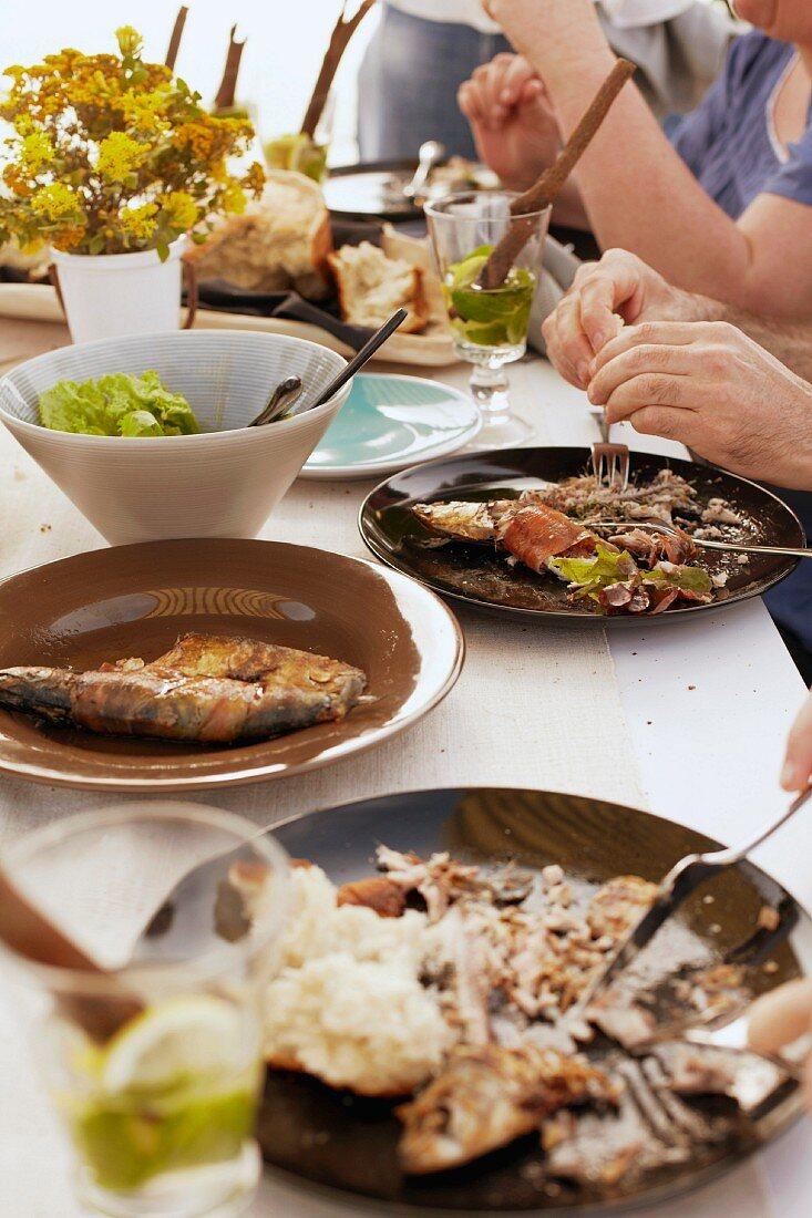A table laid for a meal with barbecued fish, salad and bread