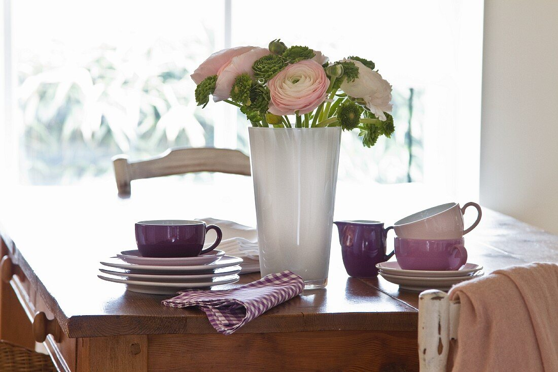 A wooden table with stacked crockery; in the centre is a decorative bunch of flowers including ranunculus