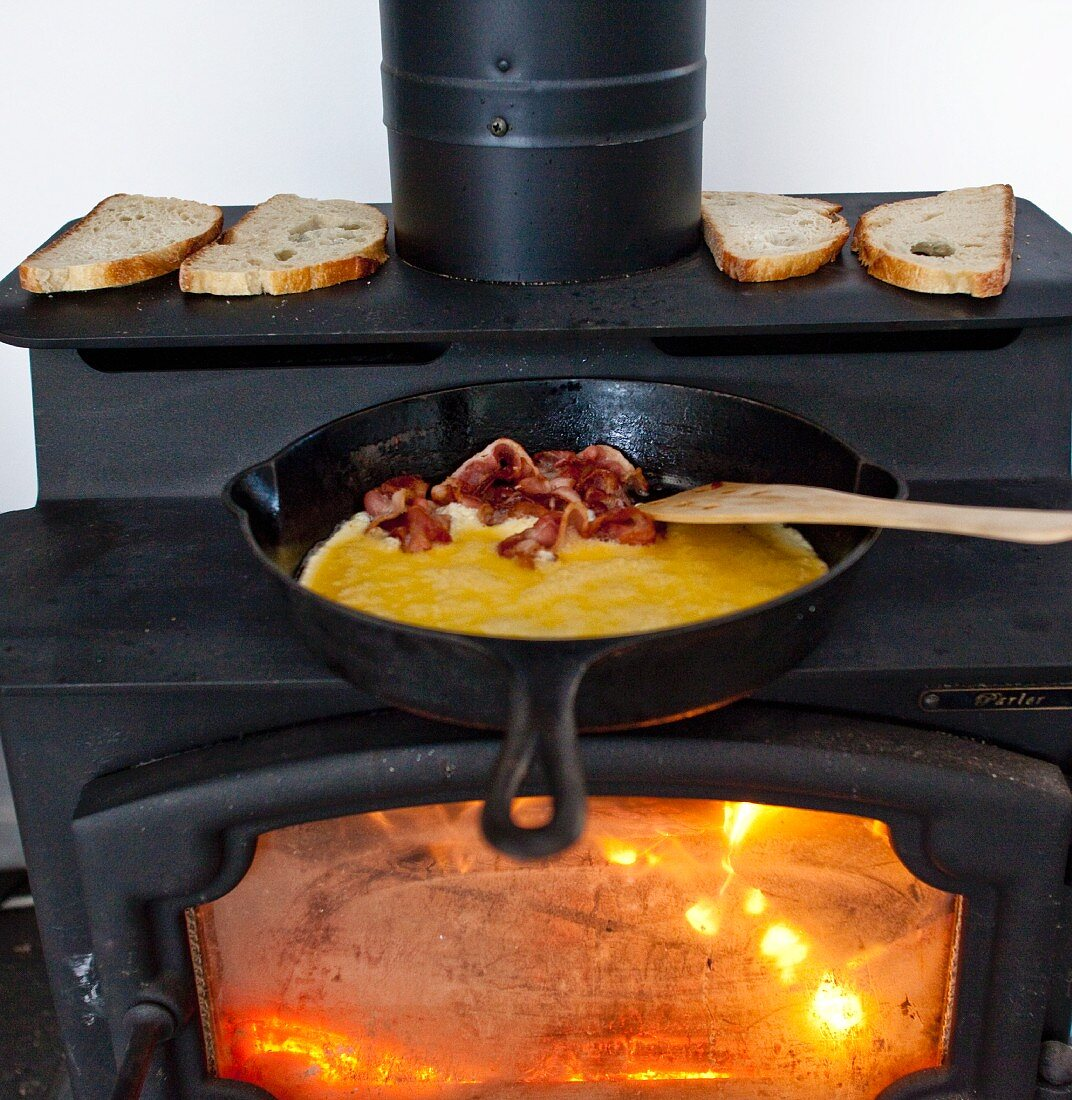Eggs and Bacon Cooking in a Cast Iron Skillet on a Wood Burning Stove; Bread Toasting on the Stove