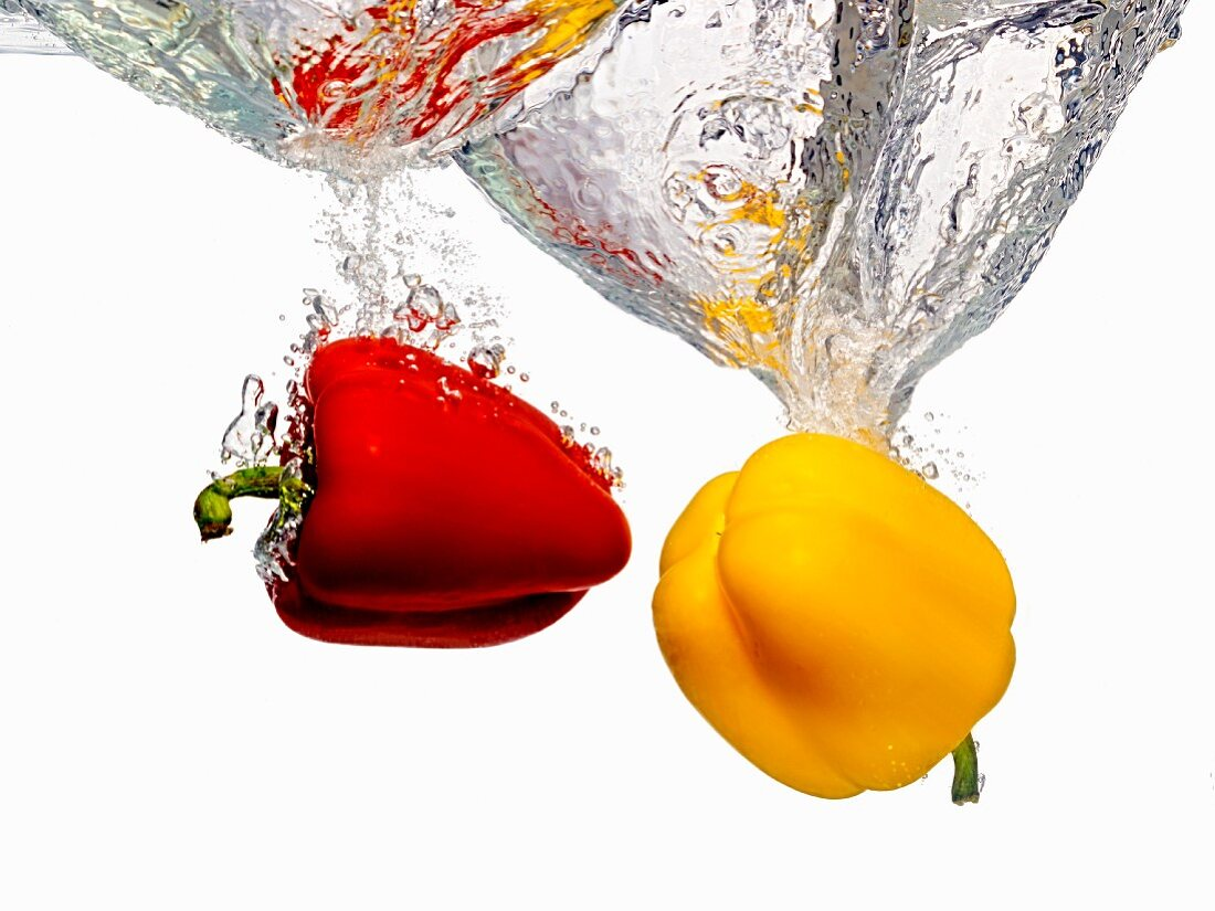 Red and Yellow Bell Peppers Splashing into Water