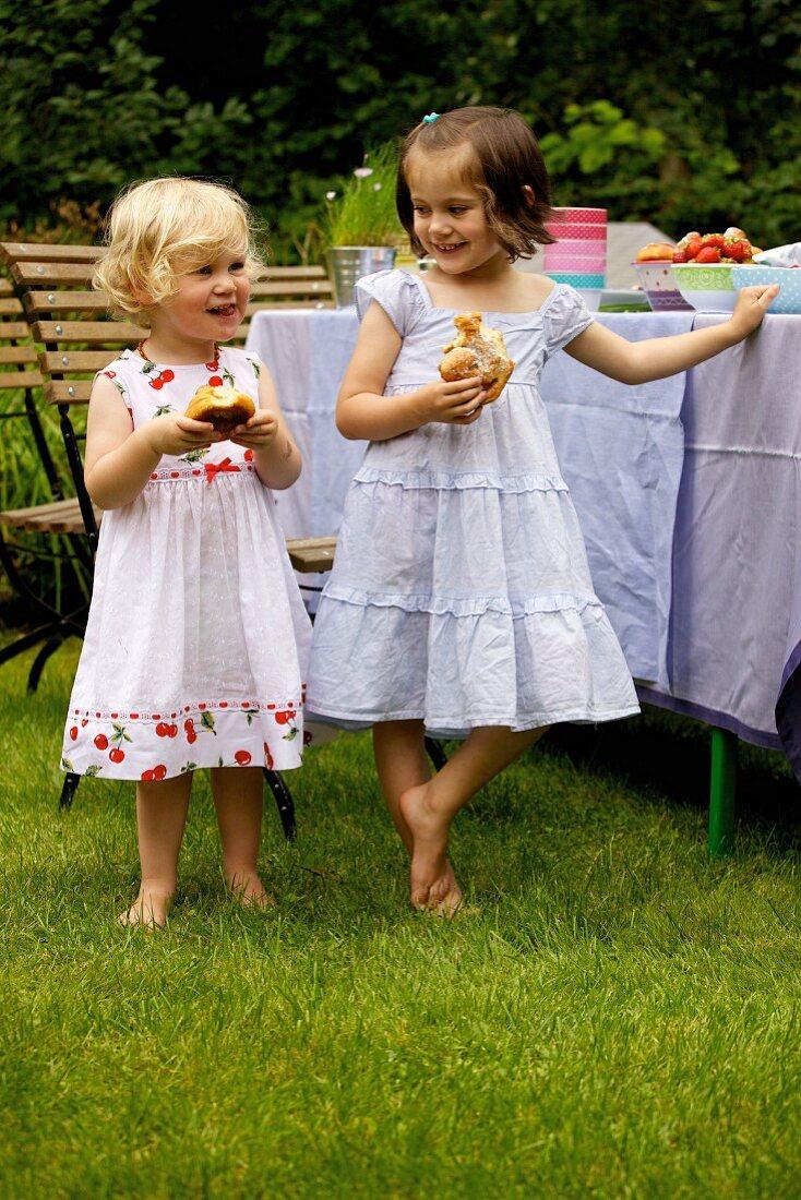 Two girls eating kanelbullar (Swedish cinnamon whirls) outside
