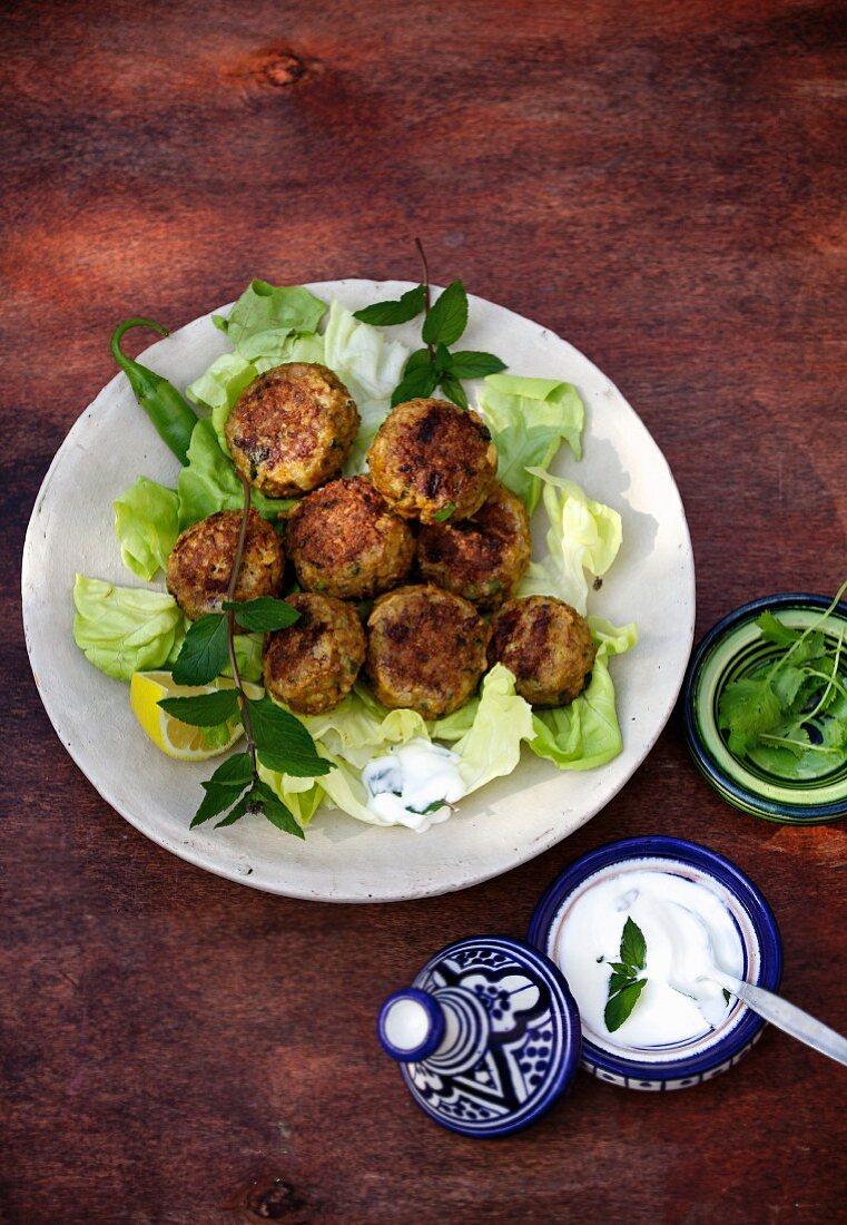 Köfte (Turkish meatballs) on a bed of lettuce leaves with mint yoghurt