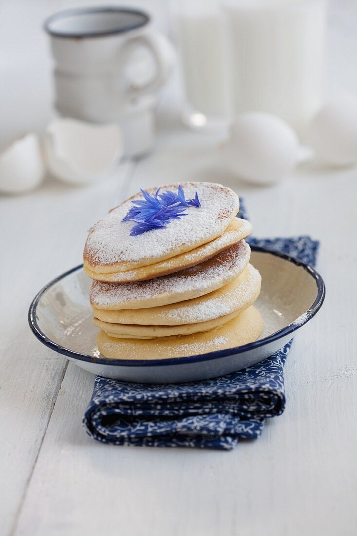 Pancakes with icing sugar and cornflower petals