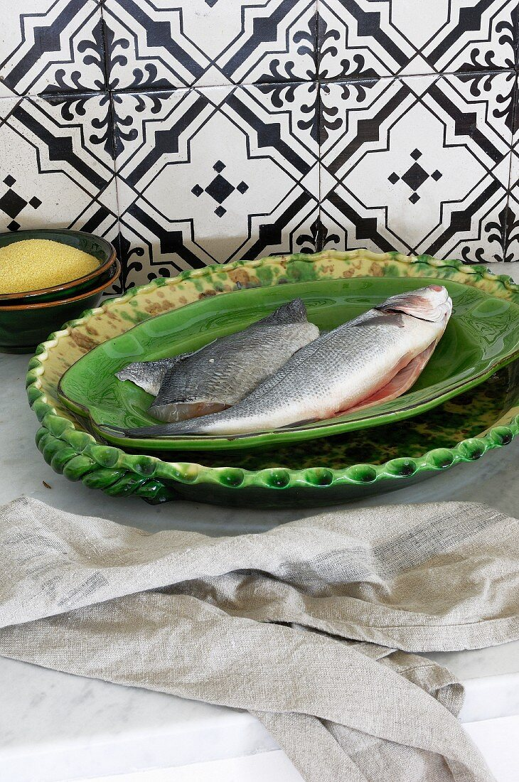 Two raw fish on a green ceramic plate
