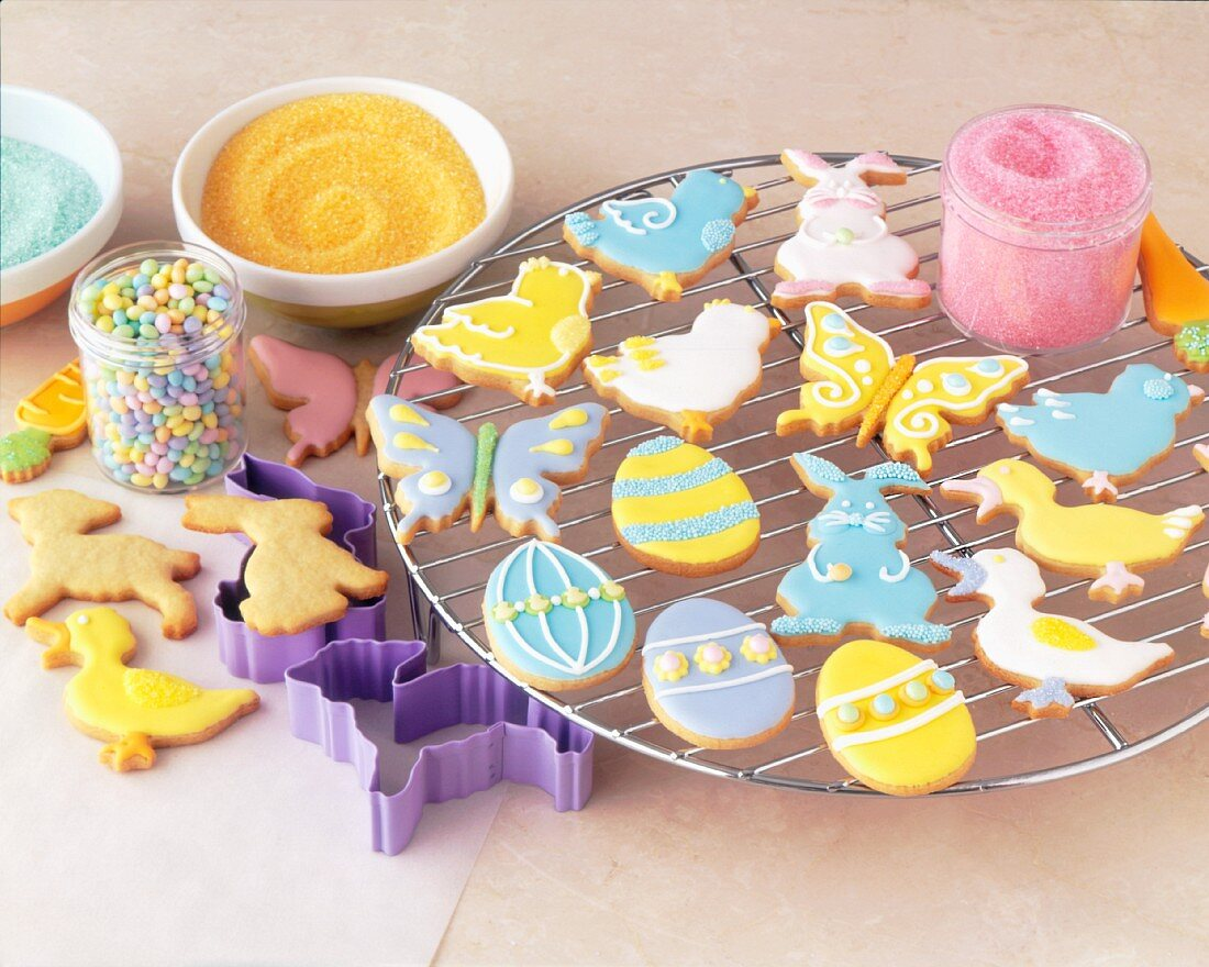 Assorted Decorated Easter Cookies on a Cooling Rack with Sprinkles and Cookie Cutters