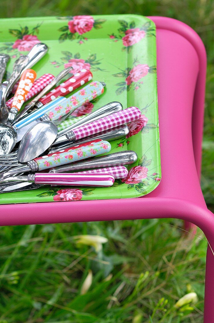 Colourful cutlery on a floral tray in the garden