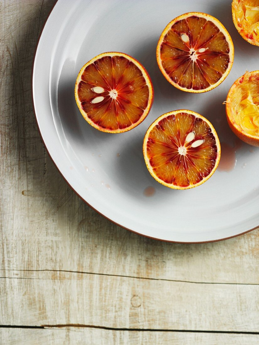 Several Sanguinello blood oranges, some cut in half and some with the juice squeezed out