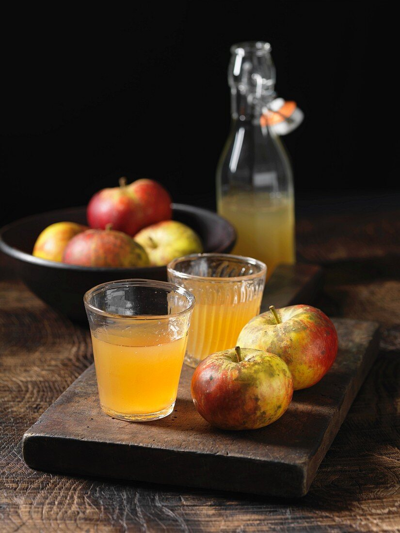 Apples and glasses of apple juice on a wooden tray