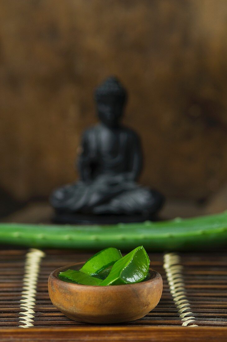 Sliced aloe vera shoots in front of a Buddha figurine