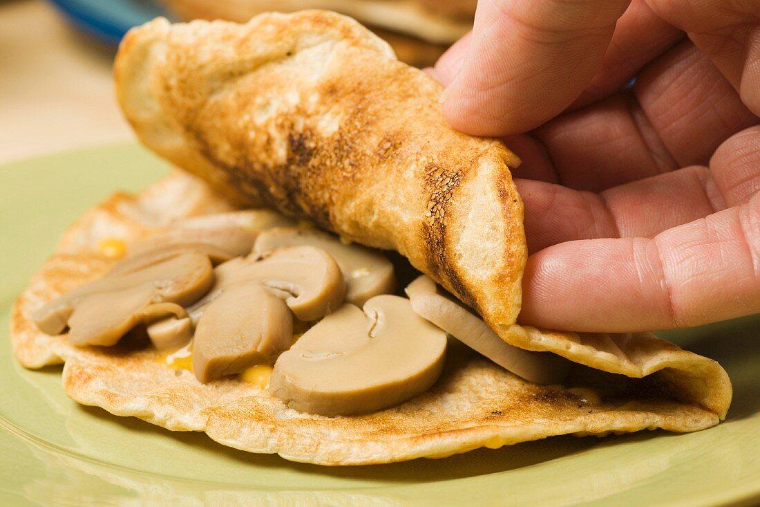 Hands Folding an Oatcake Over Mushrooms