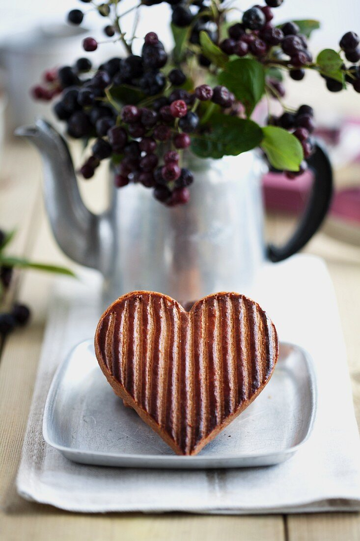 A striped heart-shaped biscuit in front of a bunch of aronia berries