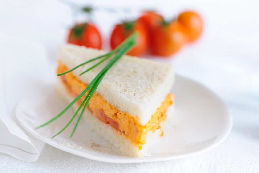 Sandwich triangle filled with tofu and tomato spread, garnished with chives