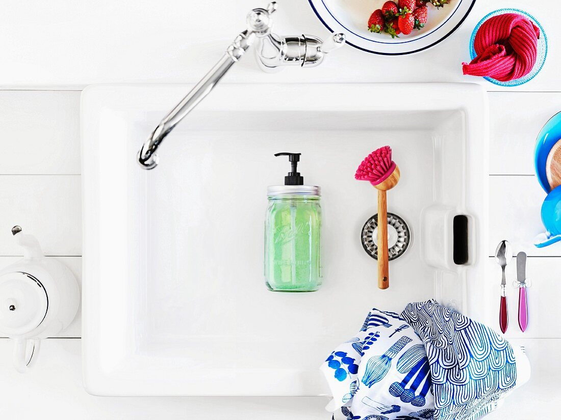 Soap dispenser hand-crafted from preserving jar lying in vintage sink