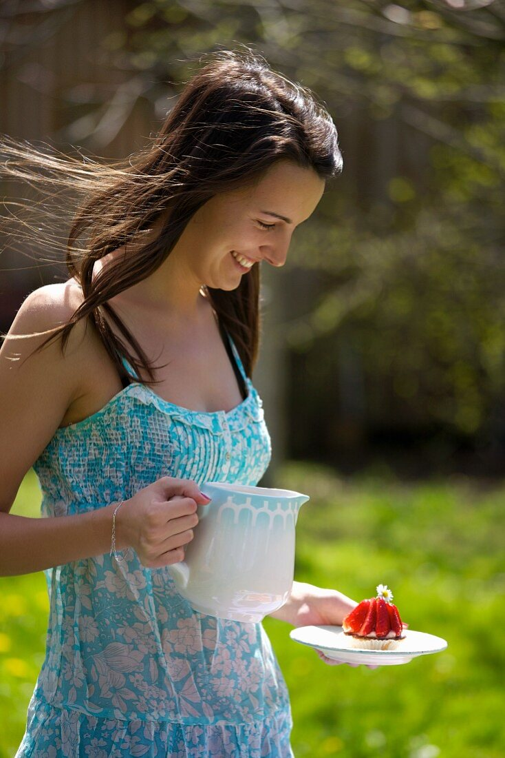 A young woman with a milk jug and a strawberry tart outdoors