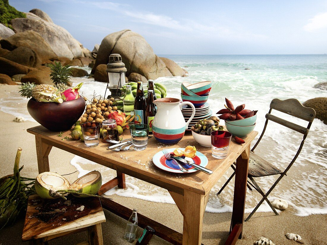 A table by the sea holding exotic fruits, drinks and crockery