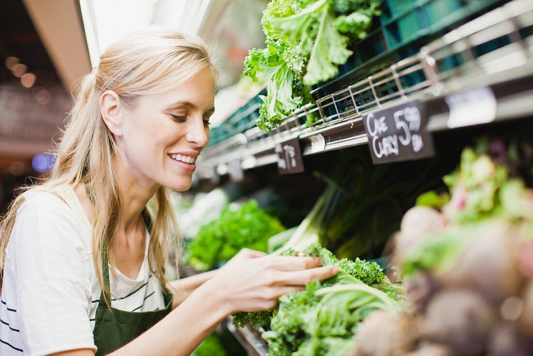 A sales assistant checking the lettuce in the vegetable section