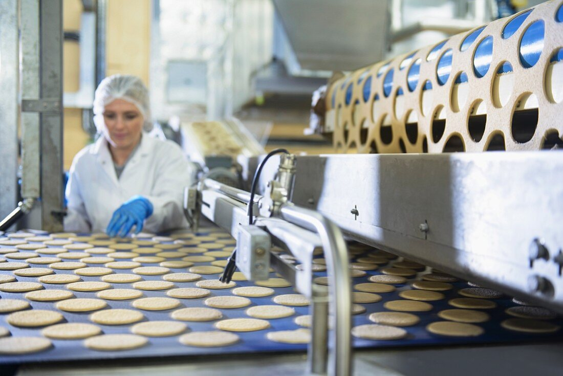 A worker sorting biscuits in a factory