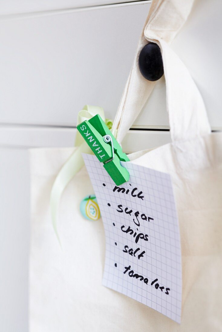 Clothes peg clipping shopping list to cloth bag
