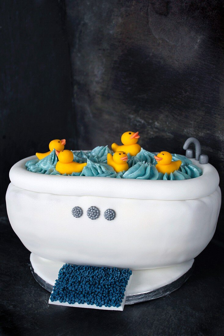 A cake decorated in white fondant to look like a bathtub with rubber ducks